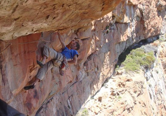 Dave Birkett chalking up on the crux roof of Remote Control, 56 kb