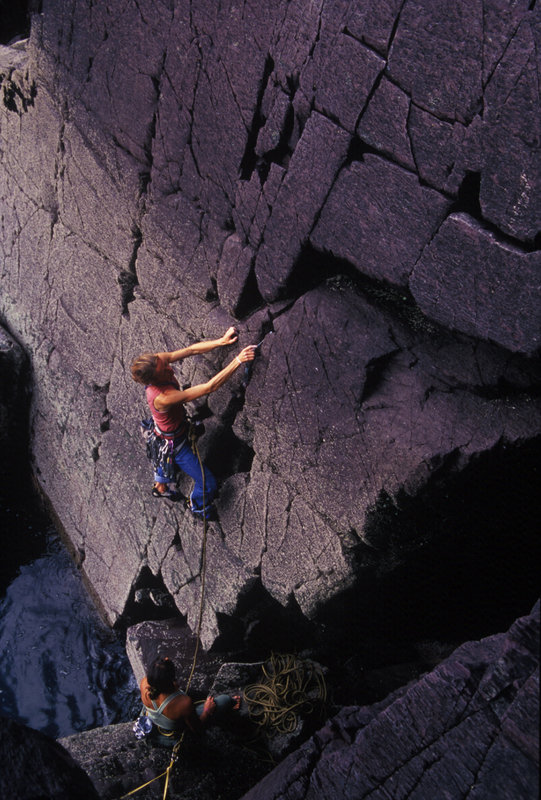 The belayer is safely attached as Libby  sets off on the delightful Red Wall, Severe, Porth Clais,  Pembroke, 122 kb