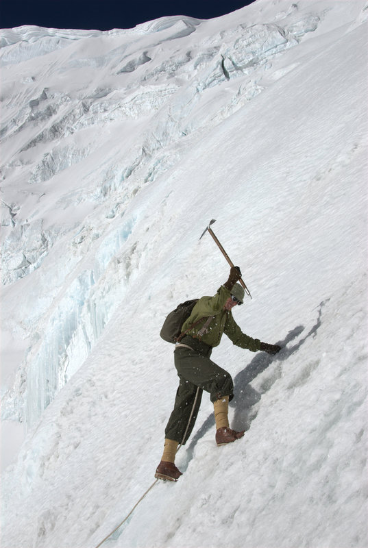 Conrad Anker, using replica 1920's clothing and equipment, cutting steps on the ice slope below Everest's North Col, 84 kb