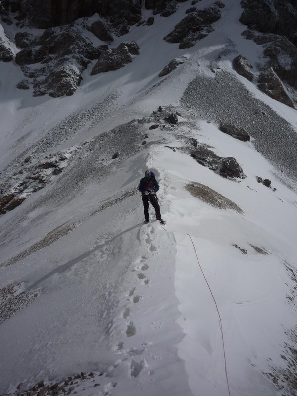 One foot in Kyrgyzstan, one foot in China:  Robert Taylor on the ridge traverse leading to the summit of Mur Samir.  Photo Copy, 83 kb