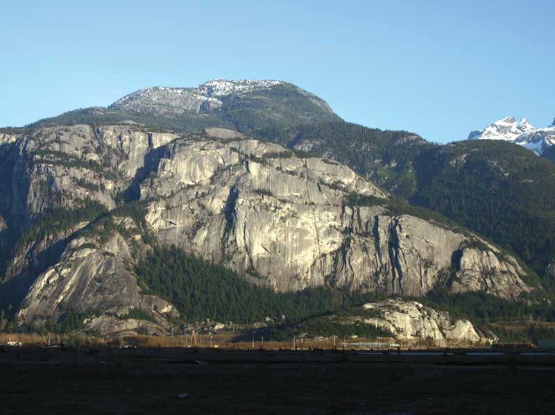 The Chief, as seen from the Squamish estuary. The main bouldering zone is in the forest directly below the whitish wall., 51 kb