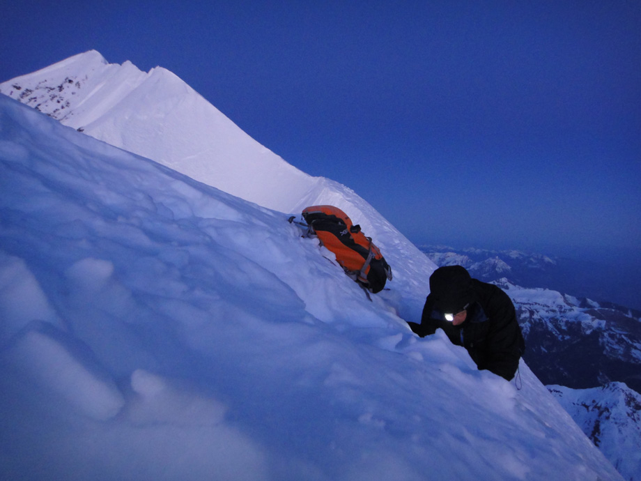 Jack Geldard digging a snow tunnel in the summit ridge of the Eiger. The summit is visible behind and to the left., 148 kb