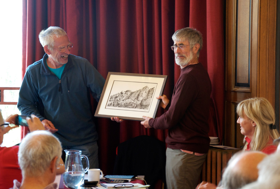 Scott Titt, the new BMC President hands Rab Carrington the retiring BMC President, a Phil Gibson crag drawing., 180 kb