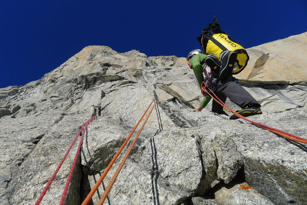 Miles Perkin looking up at the crux rock wall on Divine Providence, Grand Pilier d'Angle, 251 kb