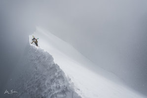 [A Guiding light. Caught in a storm on the classic Mönch SE Ridge. © John Thornton]