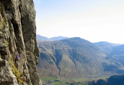 Climber on Inertia (HVS 5a), Gimmer Crag, Lake District. The big corner is The Crack (VS 4c)