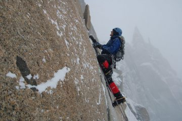 Climbing the crux slab on the Arête des Cosmiques