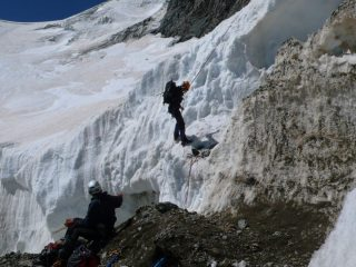 Abseiling over a bergschrund on the Violettes Glacier