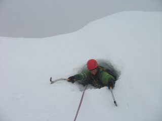 Climbing through the hole in the cornice of White Shark (IV,4), Aonach Mor