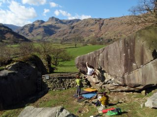 Climber's on The Overhang (V5) with the Langdale Pikes in the distance.