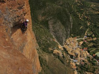 Climbers high above Riglos village on the Murciana route