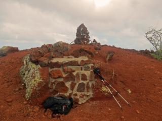 Lady Hill Summit cairn with assorted footwear. foreground shows letterbox containing log book and rubber stamp
