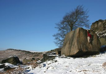 Lone boulderer latching the top of Deliverance at a deserted Stanage Plantation, Boxing Day 2004