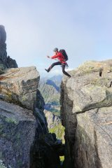 Clay Conlon jumping and praying on the final leap towards the summit of Vågakallen in Lofoten.