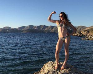 Cara Beynon flexing after sending Titis Blues 6b+ on Kalymnos