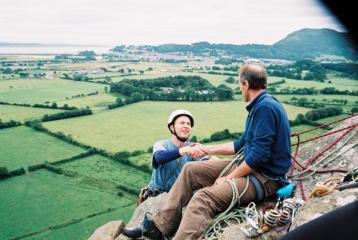 Mike welcoming Neil to the top of 4th pitch Christmas Curry (250ft Severe) Tremadog Wales.