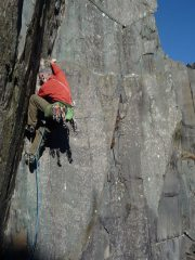 1st ascent: Using a slippery jam to reach holds on the first ledge