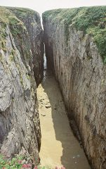 Huntsman's Leap in Pembrokeshire, with a rare covering of sand at is base.