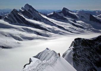 Climbers on the Monch summit ridge. Finsteraarhorn, Gross Grunhorn and Fiecherhorn in the background